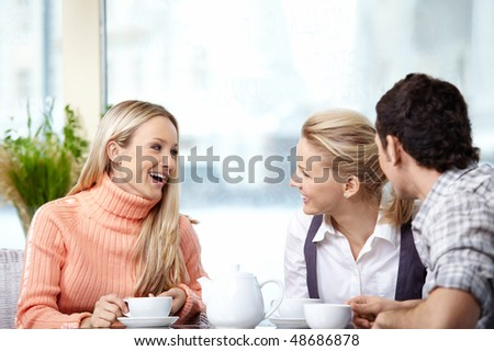 Smiling people drink coffee in the foreground - stock photo