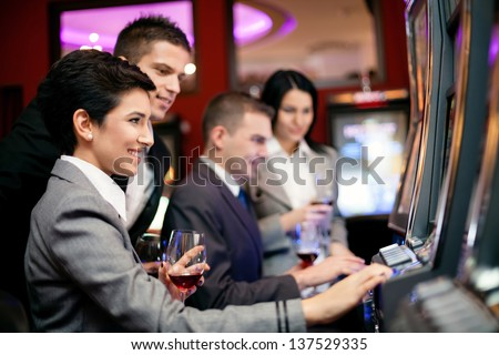 smiling people gambling on slot machines in the casino - stock photo