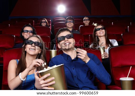 Smiling people in the cinema - stock photo