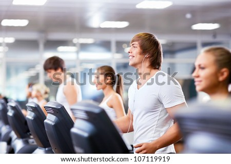 Smiling people on treadmills at fitness club - stock photo
