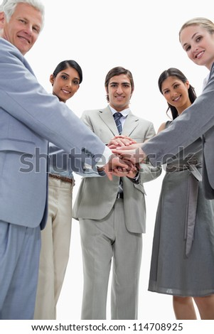 Smiling people putting their hands on each others against white background - stock photo