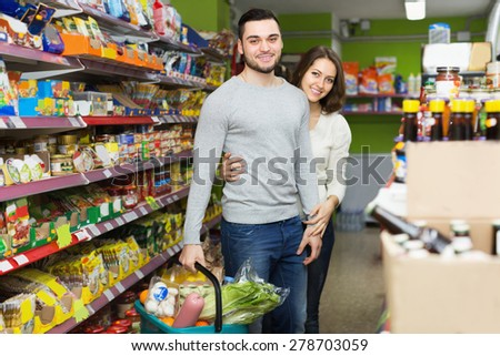 Smiling people standing near shelves with canned goods at shop - stock photo