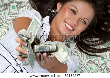 Smiling person laying in money - stock photo