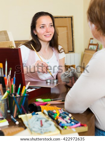 Smiling person painting image at workspace  - stock photo