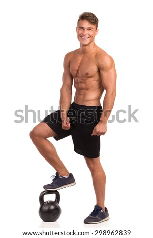 Smiling Personal Trainer And Kettle bell. Full length studio shot isolated on white. - stock photo