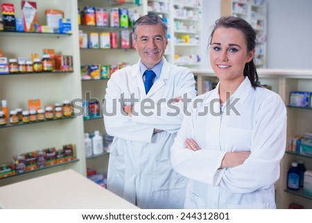 Smiling pharmacist and his trainee with arms crossed in the pharmacy