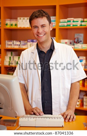 Smiling pharmacist behind the counter of a pharmacy - stock photo
