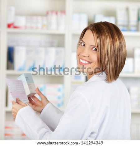 Smiling pharmacist check the prescription and medicine at the drugstore - stock photo