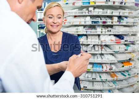 Smiling pharmacist explaining product details to customer in pharmacy - stock photo