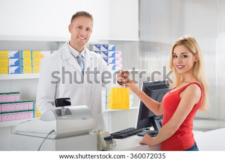 Smiling pharmacist giving medicines to female customer at counter in store - stock photo