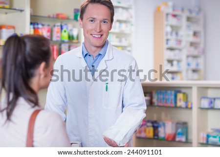 Smiling pharmacist holding a paper bag looking at camera in the pharmacy