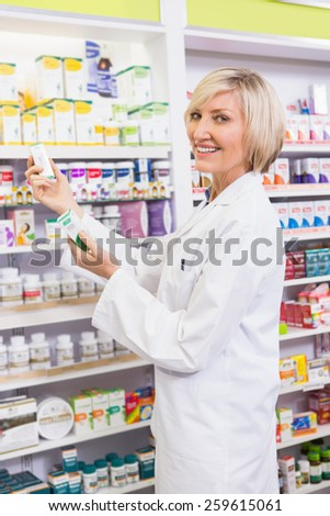 Smiling pharmacist holding boxes of medicine in the pharmacy