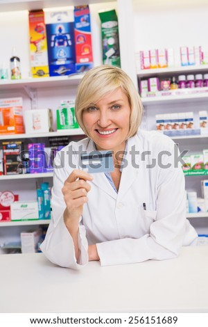 Smiling pharmacist holding credit card in the pharmacy - stock photo