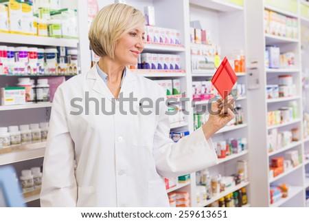 Smiling pharmacist holding envelope in the pharmacy - stock photo