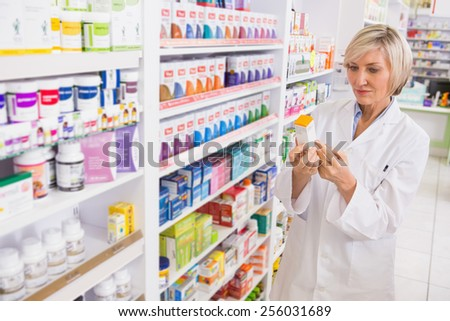 Smiling pharmacist looking at medicine in the pharmacy - stock photo