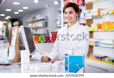 Smiling pharmacist ready to assist in choosing at counter in pharmacy