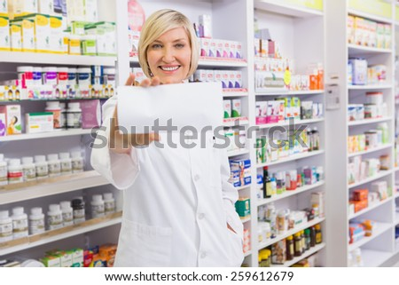 Smiling pharmacist showing paper at camera in the pharmacy - stock photo