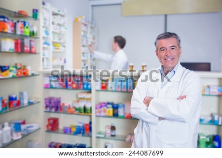 Smiling pharmacist standing with arms crossed in the pharmacy - stock photo