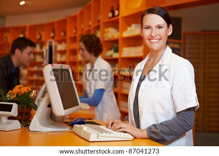 Smiling pharmacist working at computer in a pharmacy - stock photo