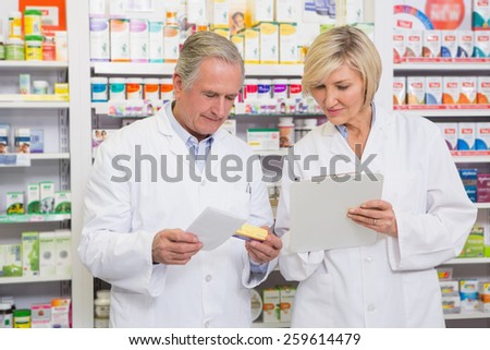 Smiling pharmacists team talking about medication in the pharmacy - stock photo