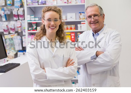Smiling pharmacists with arms crossed in the pharmacy - stock photo