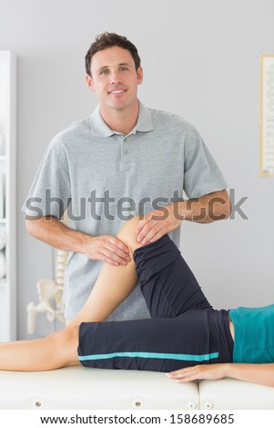 Smiling physiotherapist controlling knee of a patient in bright office - stock photo