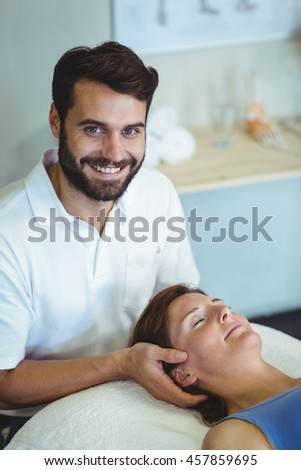 Smiling physiotherapist giving head massage to a woman in clinic - stock photo
