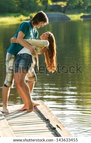Smiling playful couple having fun on pier lake - stock photo