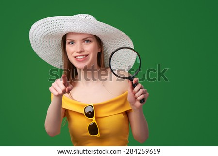Smiling playful woman wearing bright yellow dress and summer straw hat holding magnifying glass and pointing at camera, over green background - stock photo