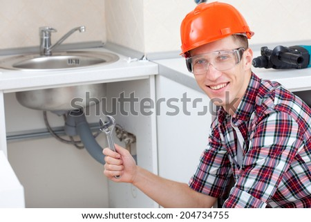 smiling plumber with a pipe wrench near the kitchen sink - stock photo