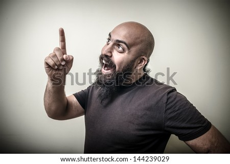 smiling pointing bearded man isolated on gray background - stock photo