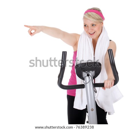 smiling pointing young woman exercising on stationary training bicycle - stock photo