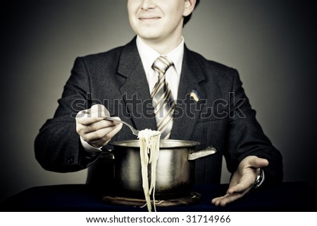 Smiling politician trying feed us with his lie. Conceptual creativity image, lies concept. Focus on hand with macaroni - stock photo