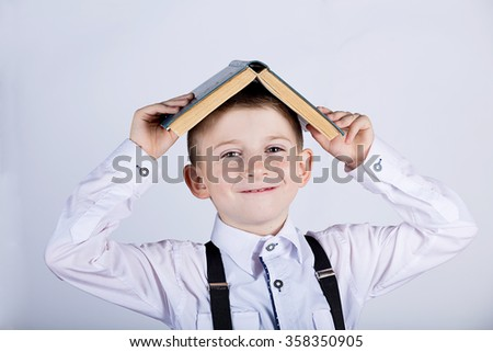 Smiling Portrait of a cute little school boy loving to learn with a open book on her head, isolated over white background. - stock photo