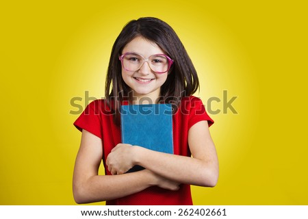 Smiling Portrait of a cute little schoolgirl loving to learn, holding with hands a book and wearing glasses isolated over yellow background - stock photo