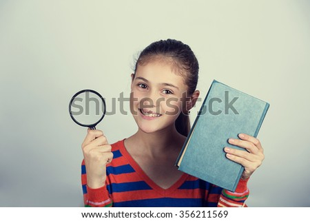 Smiling Portrait of a cute little schoolgirl loving to learn with a book and magnifying glass, isolated over yellow background. - stock photo