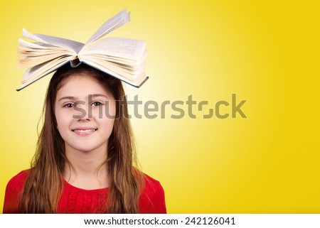 Smiling Portrait of a cute little schoolgirl loving to learn with a open book on her head, isolated over yellow background.  - stock photo