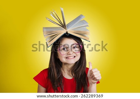 Smiling Portrait of a cute little schoolgirl loving to learn  with thumb up and a book on her head, isolated over yellow background.  - stock photo