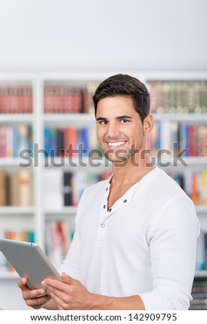 Smiling portrait of a man holding a tablet in front of the bookshelf. - stock photo