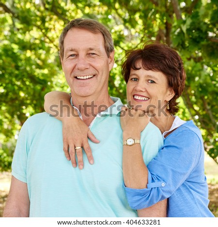 Smiling portrait of a mature couple with the wife loving embracing her husband around his shoulders and her husband smiling happily at the camera with leafy greenery behind them
