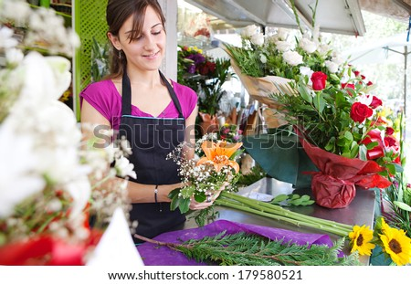 Smiling portrait of an attractive florist business woman owner at a flower shop market working and making a new floral arrangement during a sunny day. Small business owner. - stock photo