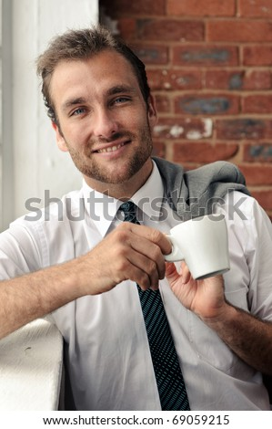 smiling portrait of an attractive man next to window - stock photo