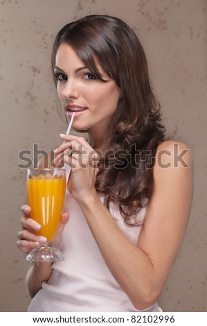 Smiling portrait of an attractive woman drinking orange juice