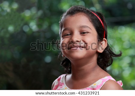 Smiling portrait of an Indian girl with outdoor background - stock photo