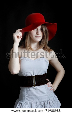 Smiling portrait of beautiful blonde caucasian girl with red hat. - stock photo