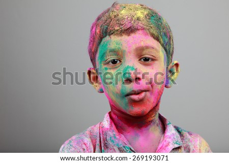 Smiling Portrait of boy with face smeared with colored powder. Concept for festival Holi - stock photo