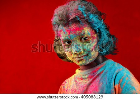 Smiling Portrait of girl with face smeared with colored powder in a red background. Concept for Indian festival Holi.