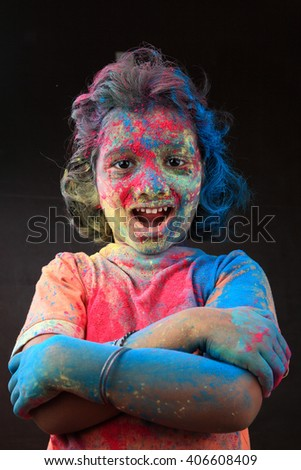 Smiling Portrait of girl with face smeared with colors in a dark background. Concept for Indian festival Holi. - stock photo