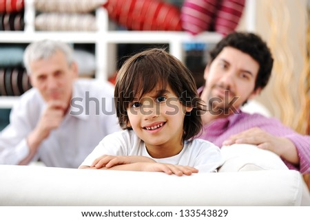 Smiling portrait of son, father and grandfather sitting on sofa at home