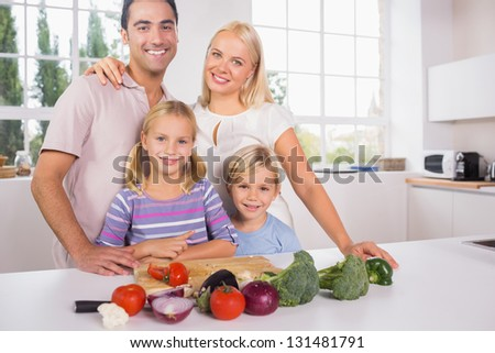 Smiling posing family cutting vegetables together in the kitchen - stock photo